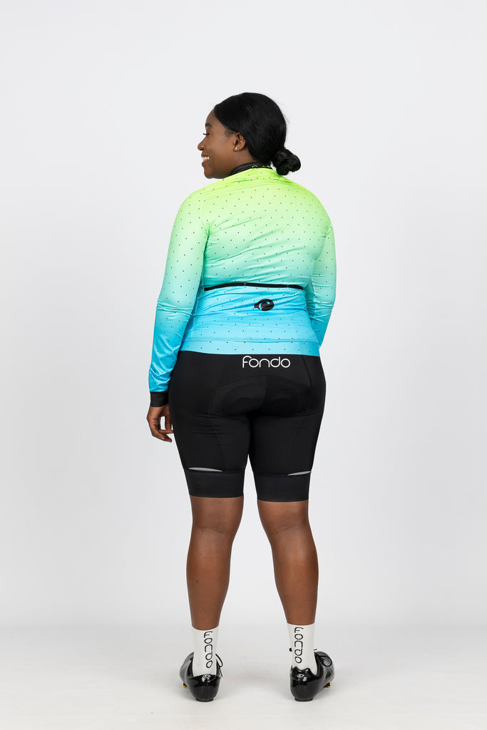 Rear view of long sleeve women's cycling jersey featuring fleece material for extra warmth and 3 large rear pockets.  Teamed with our women's cycling short black knicks with reflective tabs and fondo logo.