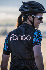 Rear view of women's cycling vest in black windproof and waterproof material with silver metallic fondo logo. Keeps cold biting winds away and packs away easily into a rear pocket. Features 2 large rear pockets and a hidden waterproof zipper pocket on the side to protect your valuables.