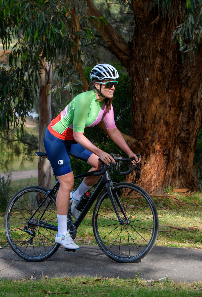 Female cyclist riding along a leafy path in her Gelato jersey and navy knicks.   Featuring comfortable and flattering women's cycling knicks and soft Italian lycra with UPF50+ sun protection.