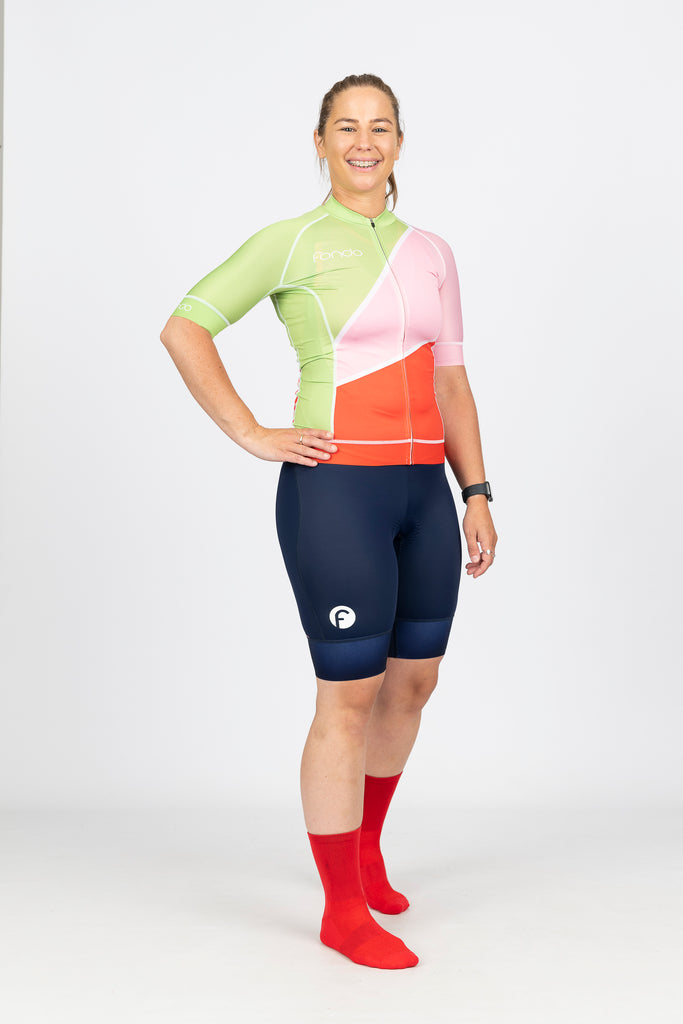 Side view of super flattering and comfortable navy blue women's cycling knicks featuring a high density women's specific Italian chamois and elastic grips to hold the knicks in place.  White fondo logos on the side of each leg.  Teamed with our bright red, green and pink Gelato short sleeve jersey to ensure you stand out in the peleton.  Jersey features soft Italian lycra and side and rear mesh panels for superior ventilation.