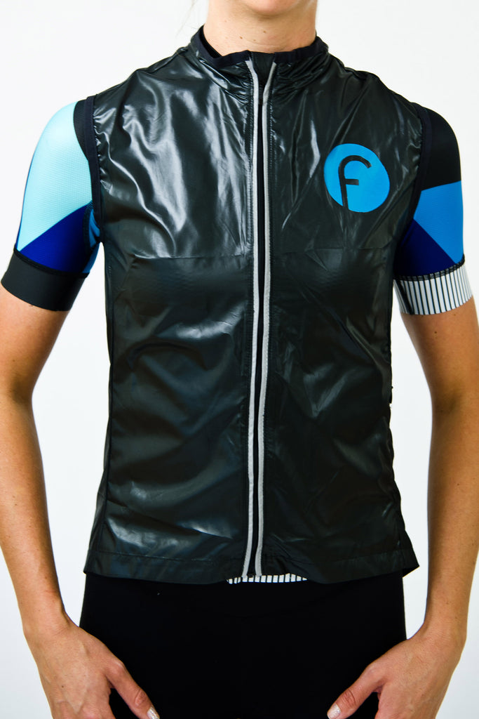 Front view of zipped up women's cycling vest in black windproof and waterproof material with blue metallic fondo logo and reflective feature on the zip. Keeps cold biting winds away and packs away easily into a rear pocket. Hidden waterproof zipper pocket on the side protects your valuables.