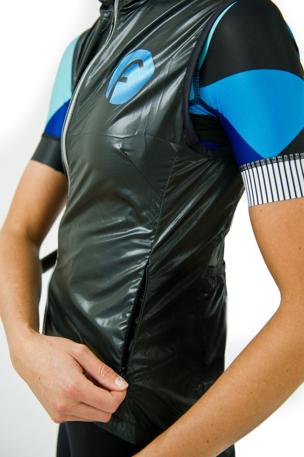 Women's cycling vest in black windproof and waterproof material with blue metallic fondo logo and reflective feature on the zip. Keeps cold biting winds away and packs away easily into a rear pocket. Hidden waterproof zipper pocket on the side protects your valuables.