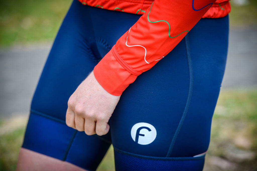 Close up view of women's cycling light packable jacket.  Shows adjustable sleeve lengths allowing extra length to tuck into gloves or can be tucked under the seam for a shorter length.   Bright red colour for extra visibility and windproof and waterproof breathable fabric.