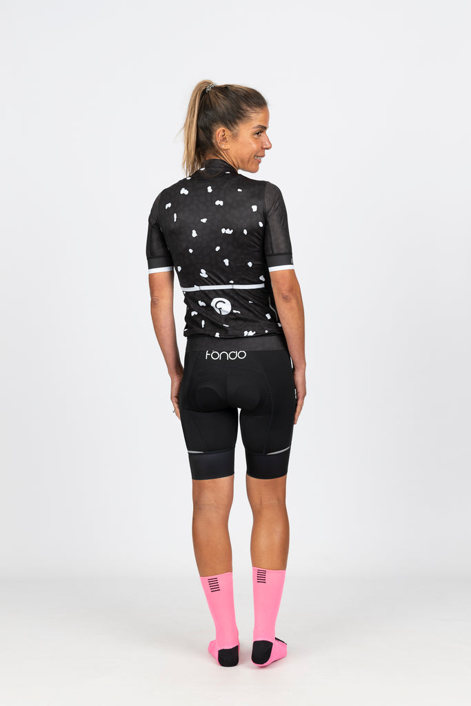 Rear view of Fondo's super flattering and comfortable women's cycling knicks with reflective tabs on the leg for added safety on the bike.  Rear view of Midnight women's short sleeve jersey showing 3 large rear pockets and white pattern accents for added visibility on the bike.