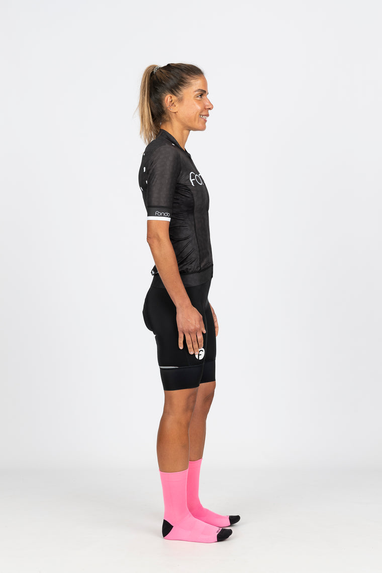 Female cyclist riding a gravel path by water in our women's short sleeve summer cycling jersey and women's specific short black knicks.  Team with bright coloured socks to really set off your outfit!