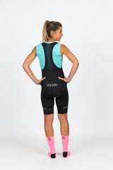 Rear view of bright aqua blue high wicking mesh cycling baselayer with high neck keeps you warm but dry on cooler mornings on the bike.  Made with soft silky mesh that offers UPF 50+ sun protection and low arm holes to avoid chaffing.  Team with our women's specific, flattering black cycling knicks with white fondo logo and high density chamois for ultimate comfort on the bike.