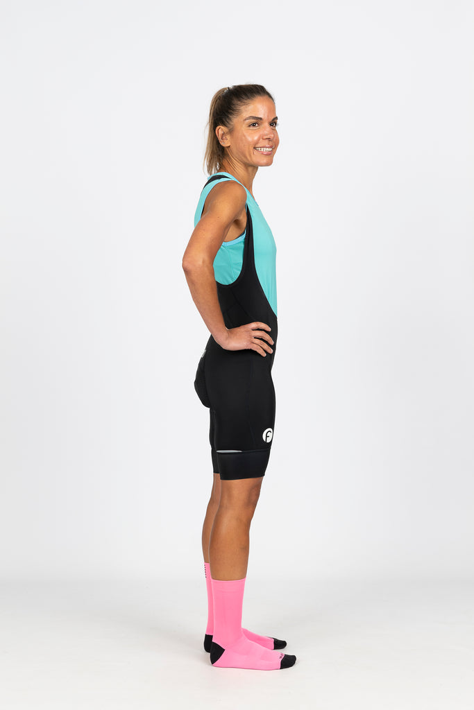 Side view of bright aqua blue high wicking mesh cycling baselayer with high neck keeps you warm but dry on cooler mornings on the bike.  Made with soft silky mesh that offers UPF 50+ sun protection and low arm holes to avoid chaffing.  Team with our women's specific, flattering black cycling knicks with white fondo logo and high density chamois for ultimate comfort on the bike.