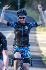 Female cyclist riding across finish line wearing women's cycling vest in black windproof and water resistant material featuring silver reflective logo and seems on the zip for extra visibility.  Worn over Fondo's honeycomb design bright women's cycling short sleeve kit it packs down easily into a rear jersey pocket. Great for keeping away the wind on a descent or chillier spring morning.