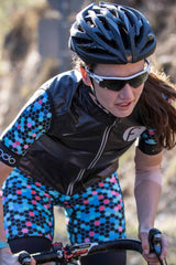Women's cycling vest in black windproof and waterproof material with silver metallic fondo logo and reflective feature on the zip. Keeps cold biting winds away and packs away easily into a rear pocket. Hidden waterproof zipper pocket on the side protects your valuables.  Great for descending in cooler conditions.