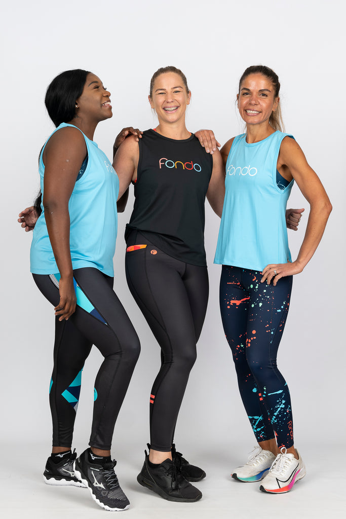 active women having fun wearing high waist leggings and relaxed fit muscle tank tops bright colours