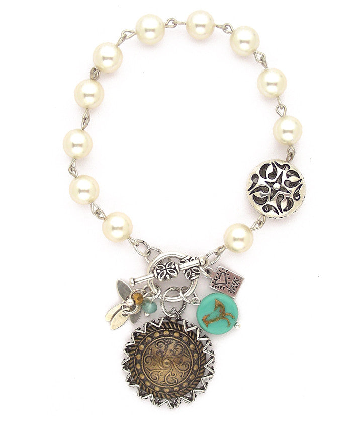 "Fun, eclectic combo of antiqued brass disc, glass pearls, copper stamped bird embedded in glass bead, pewter, sterling plated brass leaves and faceted crystal beads. Hand linked. Approx 7.5"" long."
