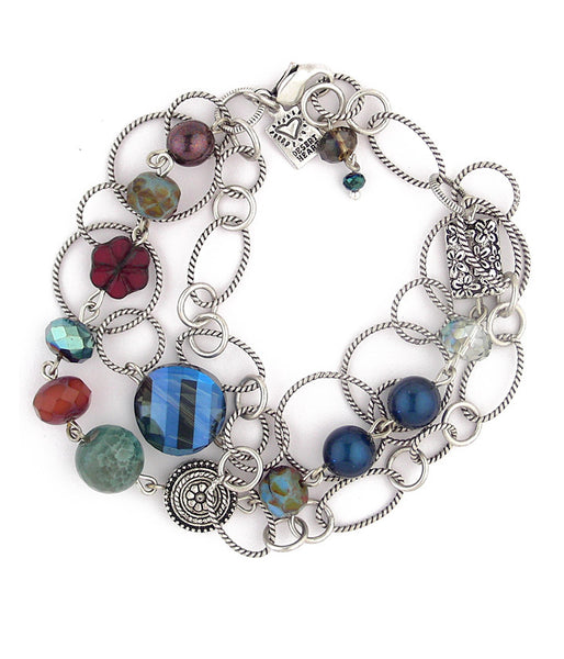 This is a nicely done 3 strand bracelet made up of sterling plated and antiqued brass, crystal, glass, agate, pewter and Swarovski petrol colored glass pearls. Fun to wear.