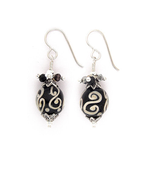 "Layers of glass create these eye catching beads, Black with cream colored swirls form the core with clear, smooth glass over that. Topped with pewter caps and a subtle, sweet collection of crystals in jet, silver, smoke and opal. Hand wrapped. A touch over 1.5"" long"