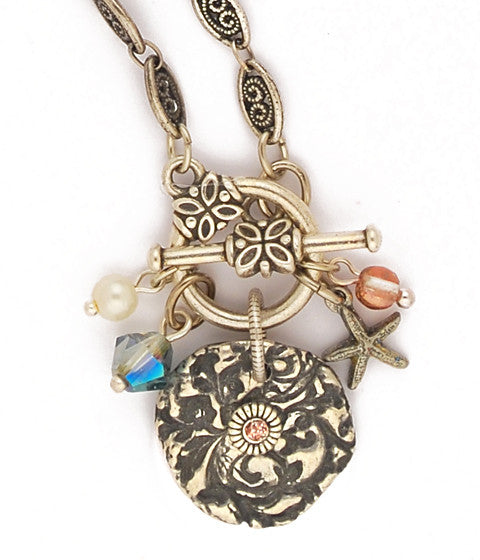 "Original cast pewter design with sparkly copper colored enamel, Swarovski creme rose glass pearls, apollo gold glass beads, iridescent blue/green crystal, sterling plated & antiqued brass starfish, woven brass chain that has been sterling plated and then antiqued. Front toggle closure. 18"" long"