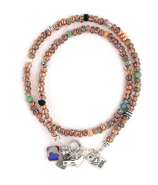"This double wrap bracelet is such fun! Made of clear glass pony beads that each have a copper coating on half of the bead. Accents of pewter and howlite and trade beads and other glass are spaced about every inch. A cluster of great charms that hang at the end provide more interest. Great color! 15""-16"""