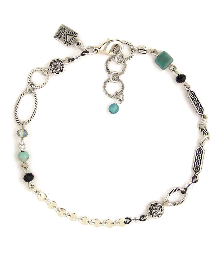 "A nice combo of elements joined together to create an interesting little work of art to adorn your ankle. Includes pewter, glass, crystal and sterling plated and antiqued brass.  9""-9.75"""