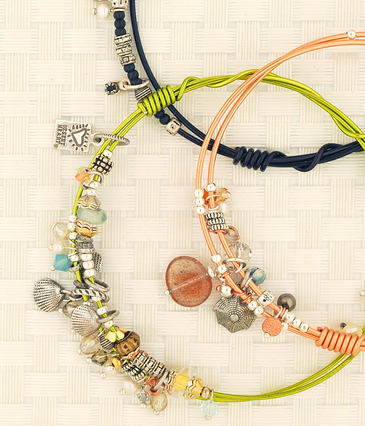 Bangle bracelets. Hand wrapped, colored, copper wire with a variety of charms and beads is glass, semi-precious and metal.