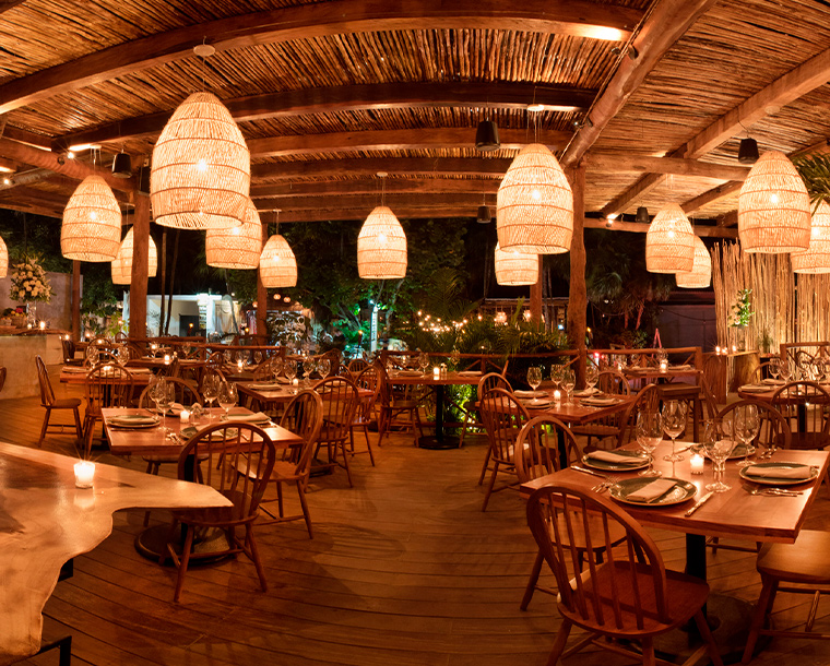 RosaNegra Tulum is the most successful culinary concept of this Heavenly destination. With a style that is a bit more rustic, natural, and bohemian than the Cancun and Mexico City's branches, its design shows care and respect for nature. Eye-catching furniture made out of parota Wood, swings, hand-woven carpets, and big artisan lamps fill the space with light and warmth. The combination results in a minimalist glamour that honors traditional handcrafts with rich textures.