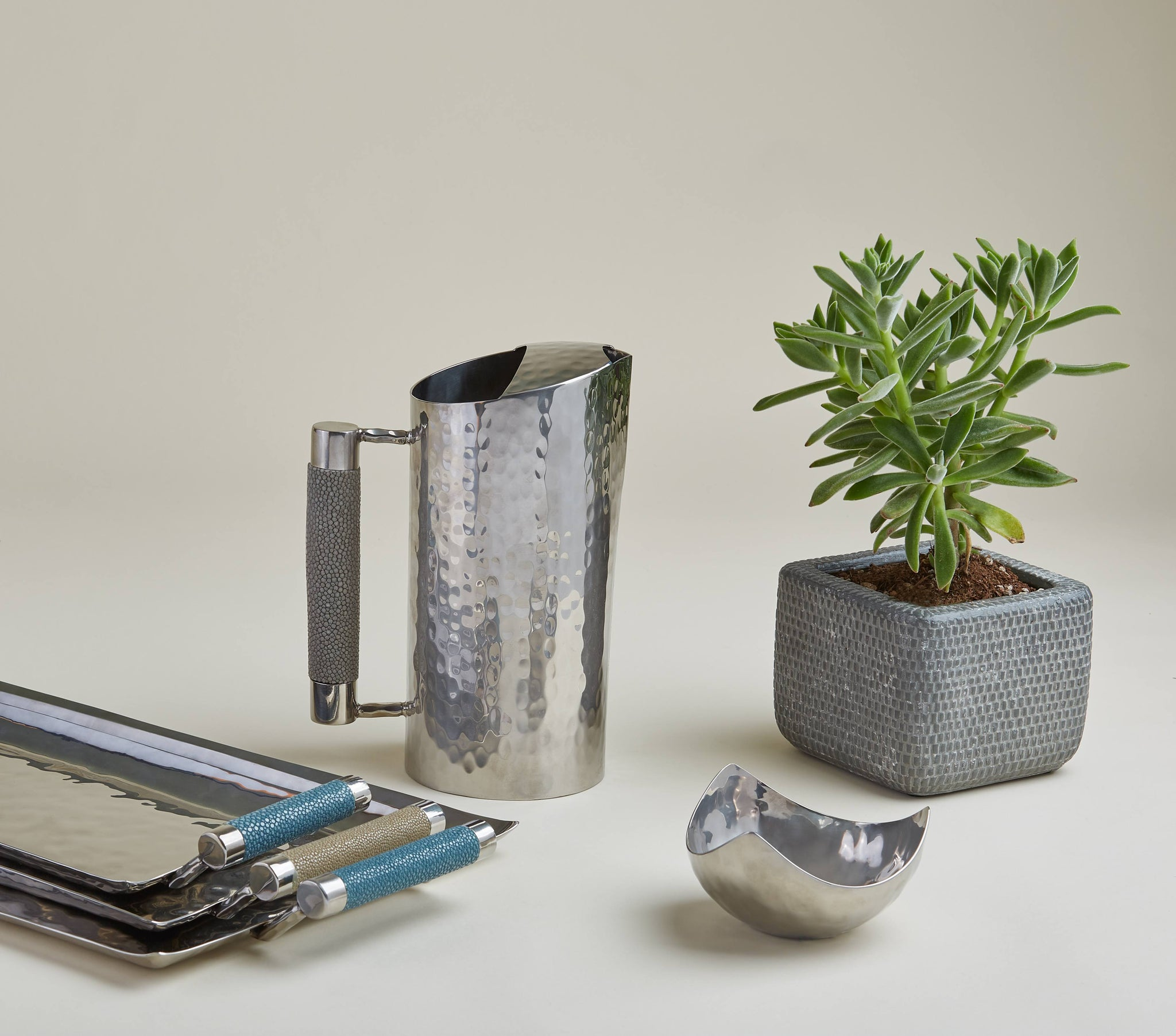 Stainless steel pitchers and trays with leather accents