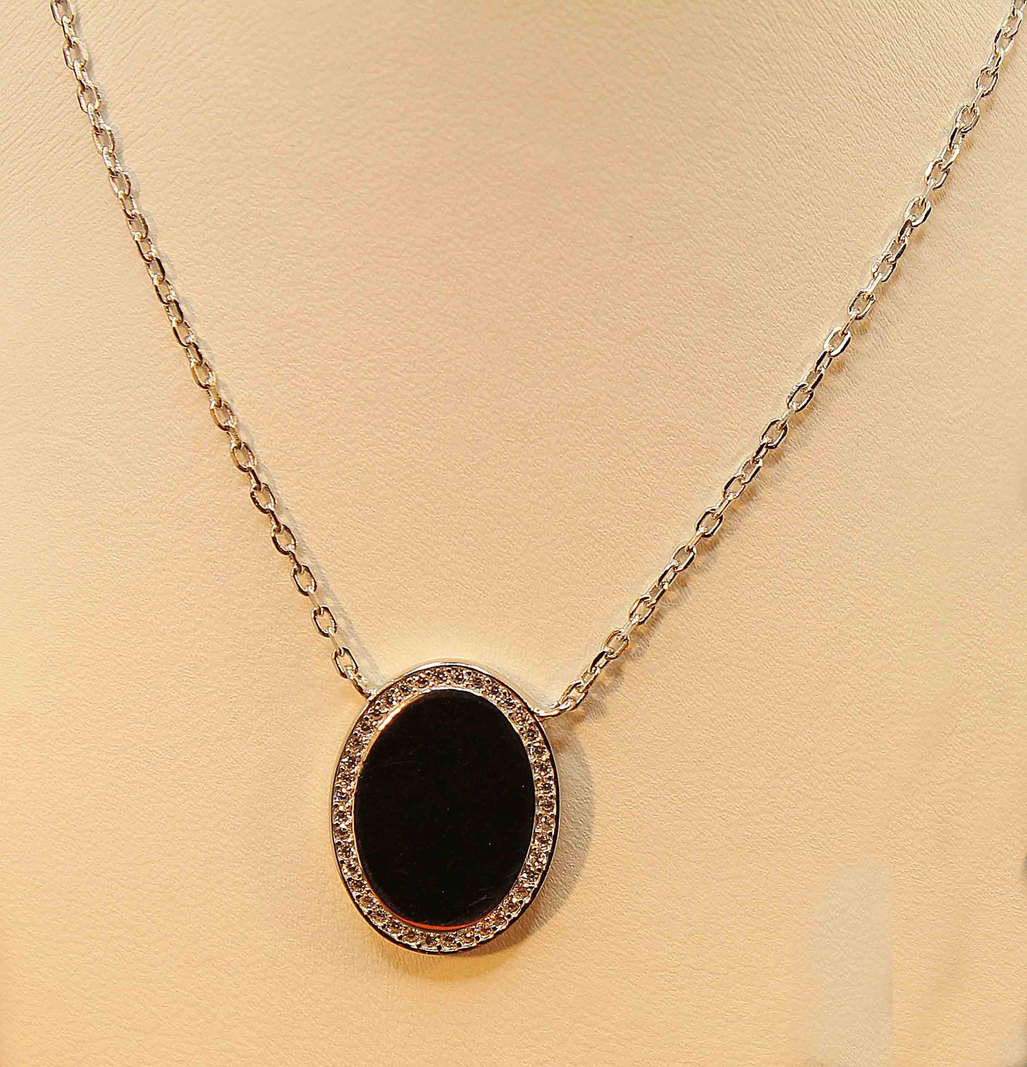 Sterling silver with rhodium finish smooth oval pendant surrounded by cubic necklace