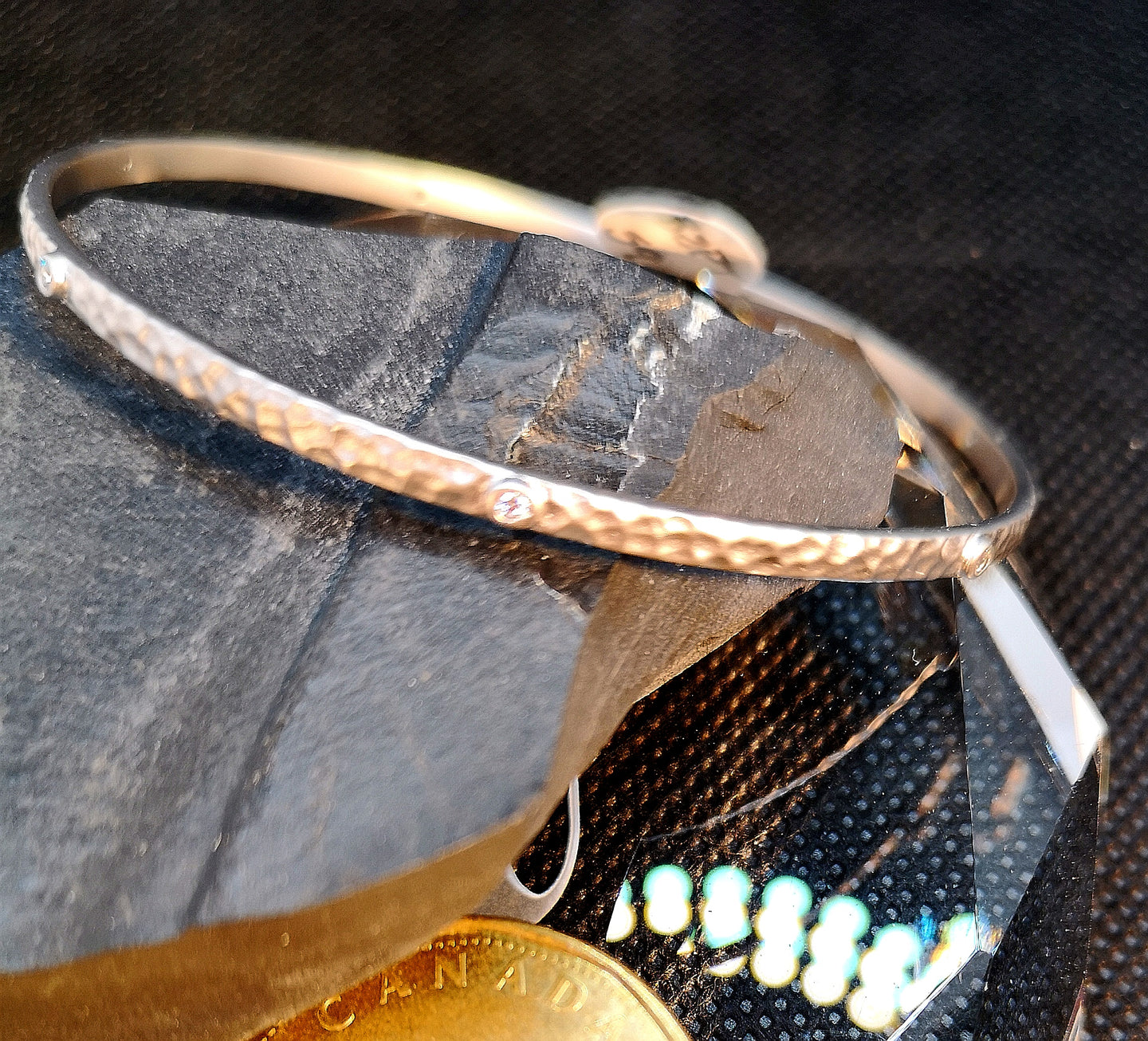 Satin finished hammered sterling silver bangle with rhodium finish and cubic