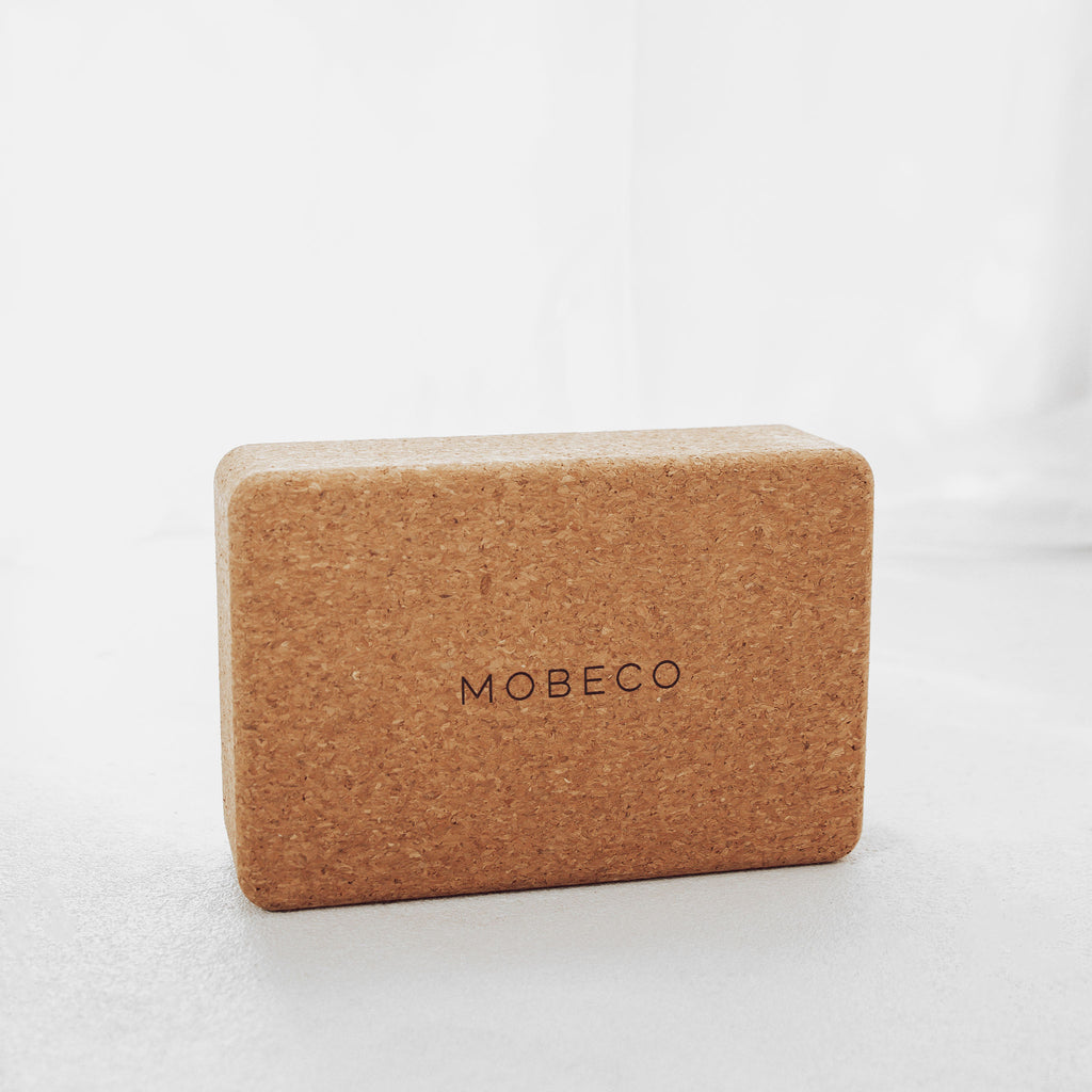 Cork yoga block with MOBECO label written on the front face.