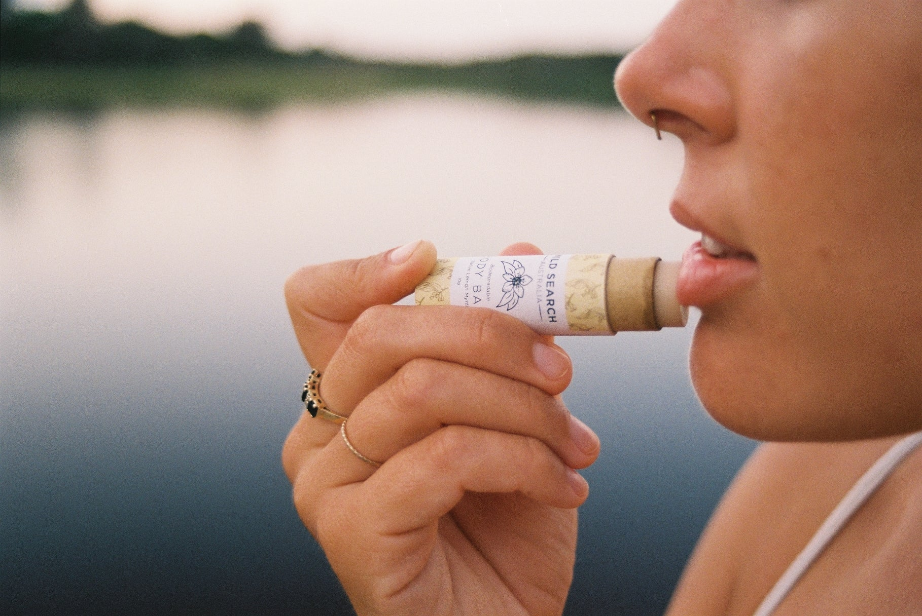 Lady puts lemon myrtle Biodegradable Lip Balm from Wild Search Australia on her lips.