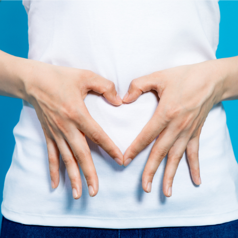 woman holding hands in heart over stomach