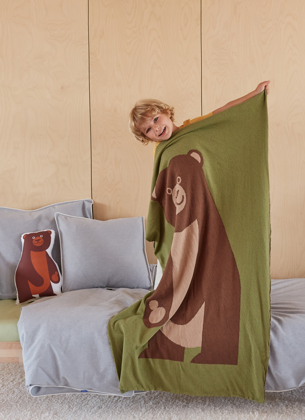 Kid smiling with large eco-friendly brown bear blanket