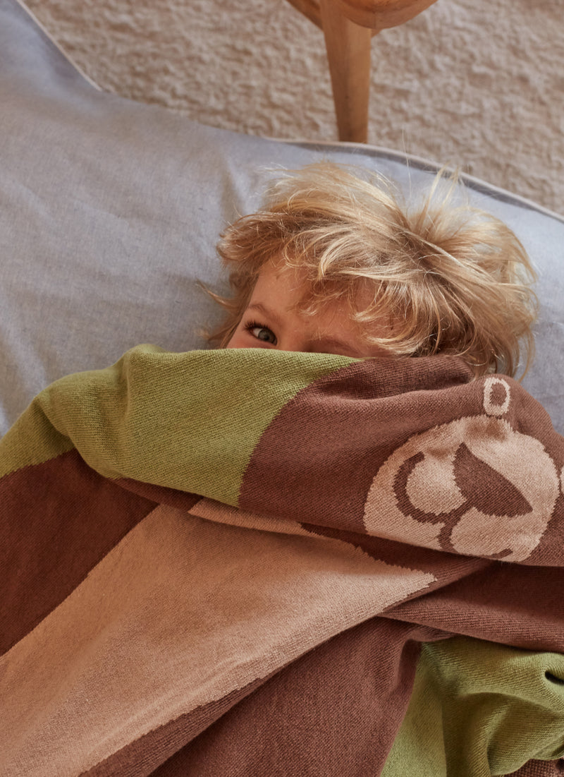 kid playing with large eco-friendly brown bear blanket