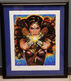 """Wonder Woman: Hell Hath No Fury"" Art Print from acclaimed artist Olivia De Berardinis.  Based on the likeness of Gal Gadot - This magnificent piece is brought to us via Sideshow and has been custom-framed. Wonder Woman sits on top a blue mat in a classic black frame.  The original acrylic-on-wood painting has been reproduced here in this hand-signed and hand-numbered print edition. This art arrives a Certificate of Authenticity signed by the artist, making this a must-have for fans of Wonder Woman."