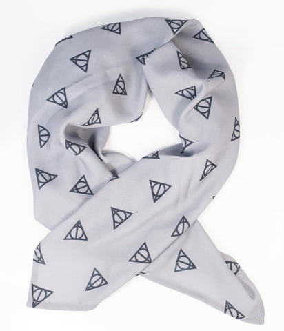Deathly Hallows Print Fashion Scarf by Unique Vintage  Show off your new charms with this delightful hair scarf from Unique Vintage in a charming collaboration with Harry Potter! Crafted in a silky chiffon, this vintage pin-up accessory features the iconic Deathly Hallows symbol printed throughout a grey backdrop. A fabulous accessory for tying up and around your divine 'do - any excuse for a little sky-high hair help!