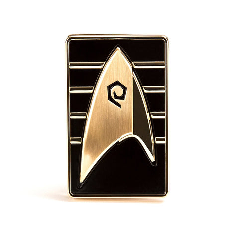 Star Trek: Discovery Cadet Badge, as seen being worn by Cadet Sylvia Tilly, features a bronze delta with the stylized Operations spiral on a black rectangle. The four gold stripes on the badge's background indicate that Cadet Tilly is in her fourth year of training to be a Starfleet officer. As with all of QMx's Star Trek badges, the cadet badge is an exact replica of the screen-used hero prop. In making the replica, we started with the 3D files the Discovery prop department used to create the original