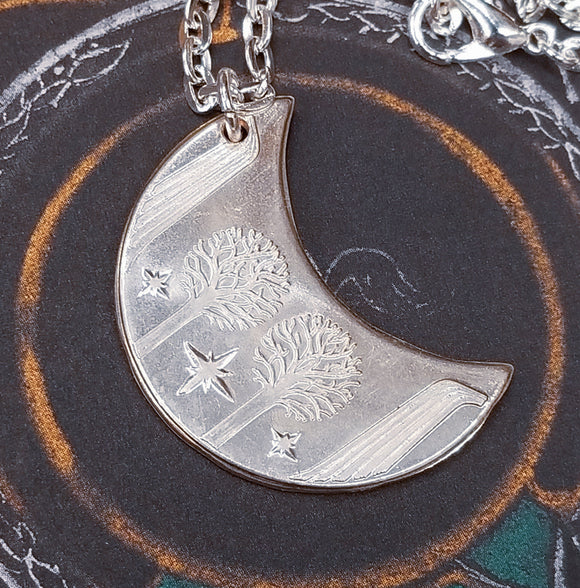 Elvish coin from Rivendell is shaped like a crescent moon. It depicts the valley containing the ancient trees of silver and gold and the three Silmarils, represented as stars. The text in Tengwar translates from Sindarin to Elrond Peredhil, Lord of Rivendell, The Last Homely House East of the Sea. It includes the date that Thorin and Company meet Elrond at Rivendell before continuing on to The Lonely Mountain.  This Rivendell Moon is crafted in celebration of The Lord of the Rings by J. R. R. Tolkien