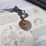 "A layered necklace containing a set of three coins from the Shire in the The Lord of the Rings.  A 30"" chain holds three coins from The Shire coins: a brass Shire Tuppence, a copper Shire Penny, and a tiny copper Shire Farthing. Coin text is inscribed in Tengwar. The coins will each feature a tree that will be one of the following variants: pine, elm, willow, and oak. The card inside provides translation of the coin text on each coin."