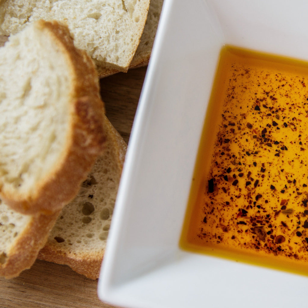 Black & Gold Smoked Chipotle Oil in a white dish next to sliced crusty bread