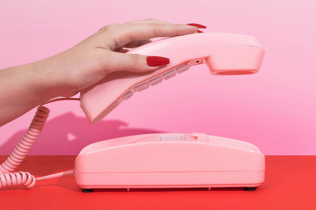 Girl wearing Instant Mani Red Coffin press-on nails Australia, picking up pink phone, with pink and red background.