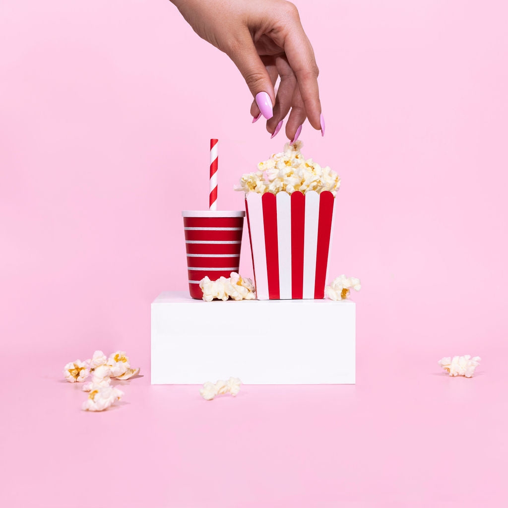 Hand reaching into popcorn wearing Instant Mani pink bubblegum press-on nails