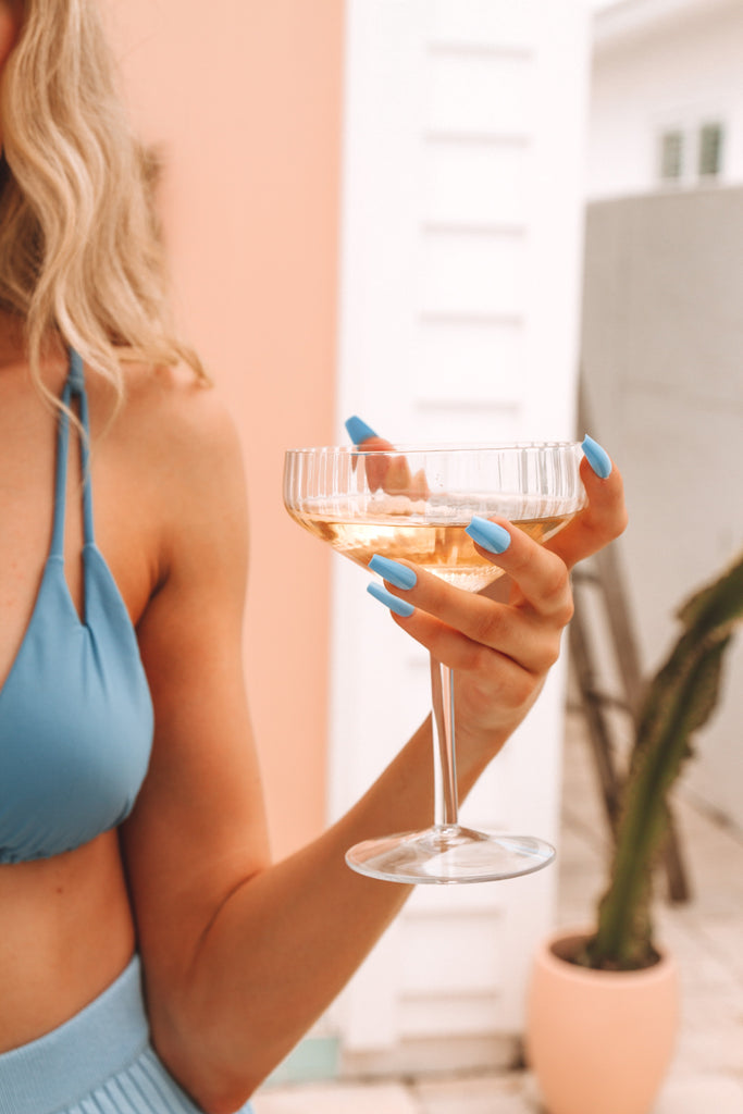 Girl wearing Instant Mani press-on blue Hvar fake nails, holding glass of champagne.