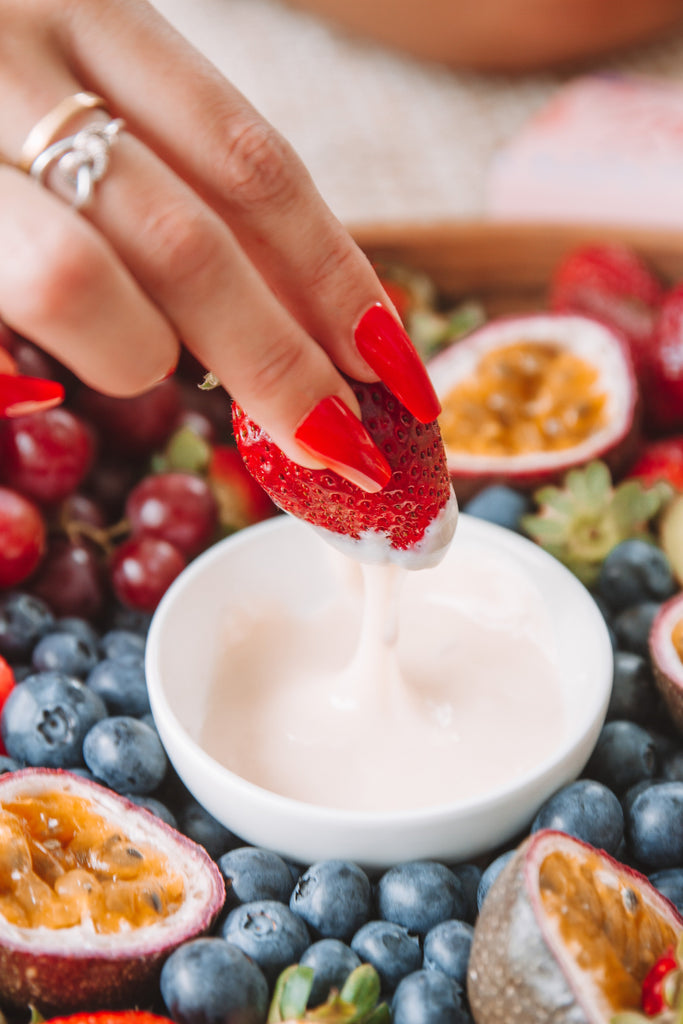 Instant Mani press-on nails in red, dipping strawberry into white chocolate fruit platter.