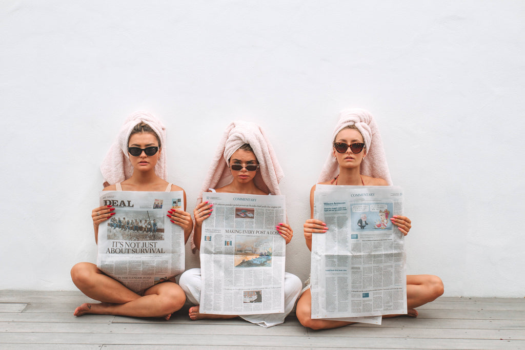 three girls reading newspaper with towels on head, wearing Instant Mani press-on fake nails.