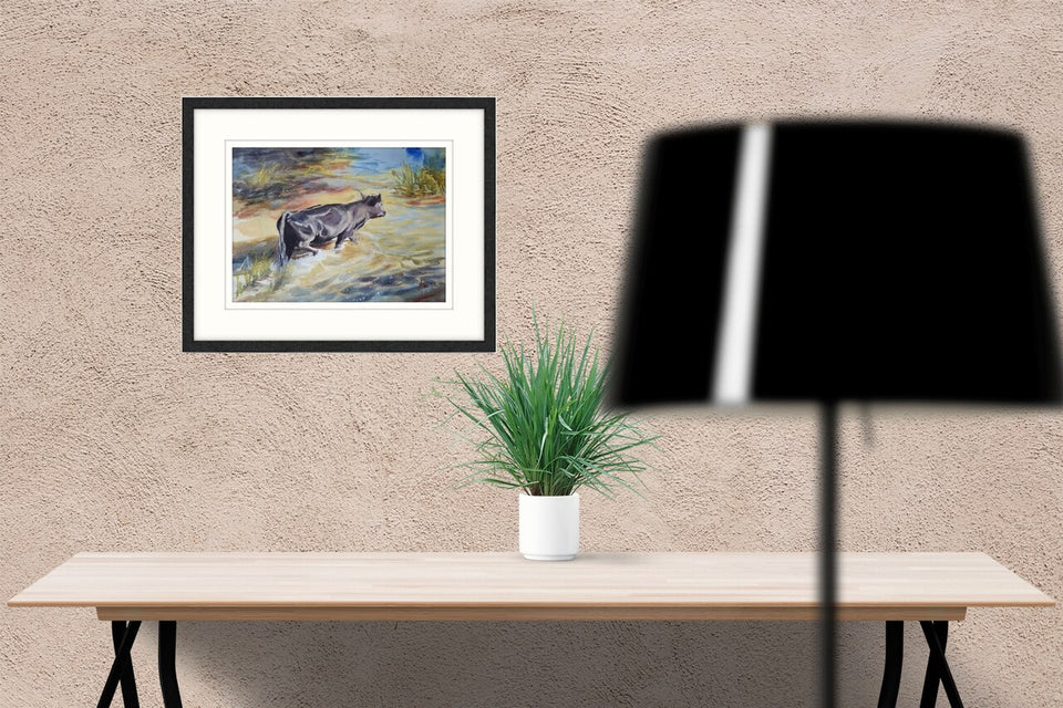 Framed and on wall watercolour animal landscape of a black cow crossing shallow water