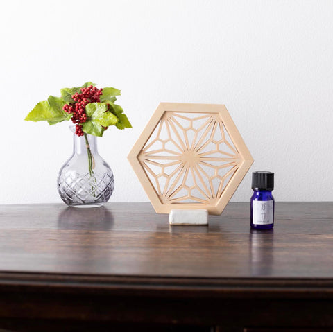 japanese wooden diffuser kumiko and blue fragrance bottle on wooden tablekiginkin