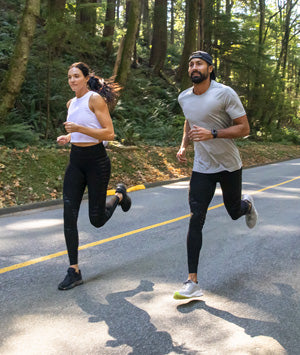 Man and woman running and wearing Stoko knee support and compression pants