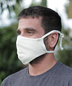 We are now offering our four tie mask with stretch. This style has four straps that tie easily behind the head and neck for a snug fit.  Mask is two layers with a pocket. Shown here in Natural.