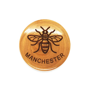 Circular olive wood magnet with bee and MANCHESTER lasered on