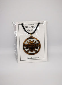 Manchester bee olive wood necklace, made in Bethlehem. Hung on black cord and in packaging