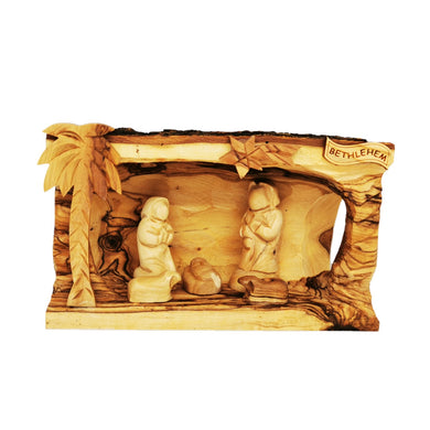 Hollowed out olive wood branch, hand carved in Bethlehem to create nativity scene. Faceless figures of Mary, Joseph, Baby Jesus and lambs. Palm tree, star of Bethlehem, natural unique grain