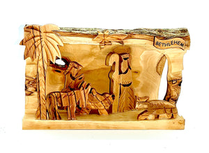 Hollowed out olive wood branch, hand carved in Bethlehem to create nativity scene. Figures of Mary, Joseph, Baby Jesus and lambs. Palm tree, star of Bethlehem, natural unique grain