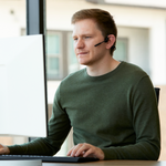 Man sitting at desk in office wearing Aftershokz OpenComm headset